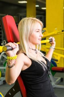 Schöne frau, die muskeln auf gymnastikmaschine biegt