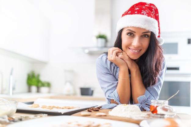 Schöne frau, die nach einem ganzen tag weihnachtsbacken weit lächelt.