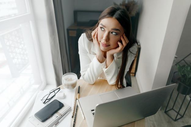 Schöne frau, die nahe hellem fenster sitzt, während sie über arbeit nachdenkt und ihren kopf hält. porträt der frau, die mit laptop-computer auf tisch arbeitet