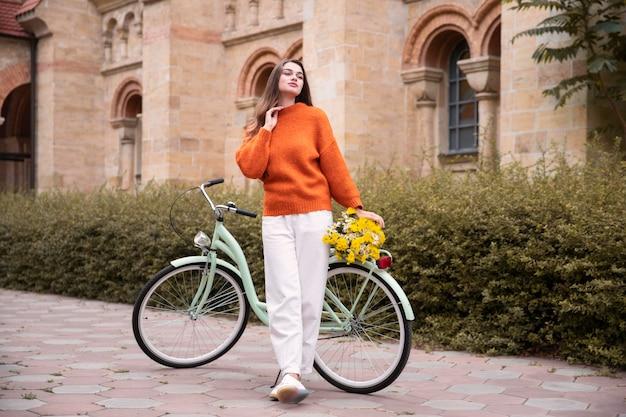 Schöne frau, die neben fahrrad außerhalb aufwirft