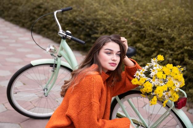 Schöne frau, die neben fahrrad im freien aufwirft