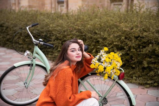 Schöne frau, die neben fahrrad mit blumen draußen aufwirft