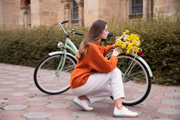 Schöne frau, die neben fahrrad mit blumen im freien aufwirft