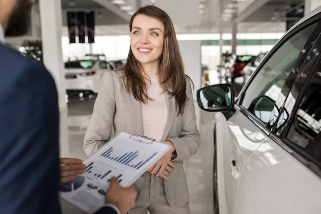 Schöne frau, die neues auto kauft