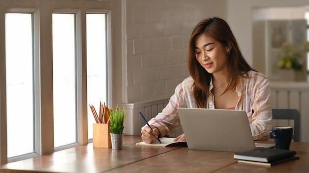 Schöne frau, die notizen schreibt / macht, während sie vor ihrem computer-laptop am hölzernen arbeitstisch über wohnzimmer-bücherregal sitzt