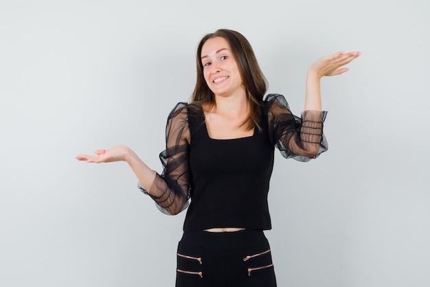 Schöne frau, die offene handflächen in der schwarzen bluse beiseite spreizt und fröhlich aussieht. vorderansicht.