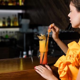 Schöne frau, die orangenfruchtcocktail an der bar trinkt