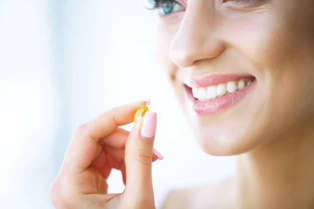 Schöne frau, die pille, medizin nimmt. vitamine und nahrungsergänzungsmittel