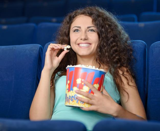 Schöne frau, die popcorn beim aufpassen des films isst.