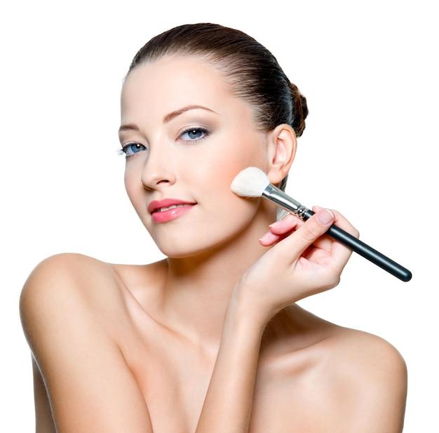 Schöne frau, die rau auf wange mit kosmetischem pinsel anwendet.