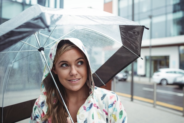 Schöne frau, die regenschirm hält