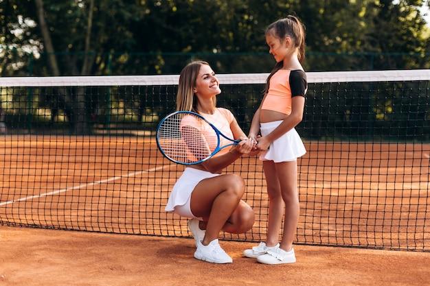 Schöne frau, die richtungen auf dem spielen von tennis gibt