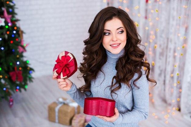 Schöne frau, die romantisches geschenk zu hause öffnet. liebeskonzept. weihnachten und neujahr feiern.