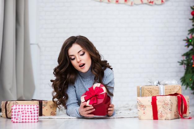 Schöne frau, die romantisches geschenk zu hause öffnet. liebeskonzept.