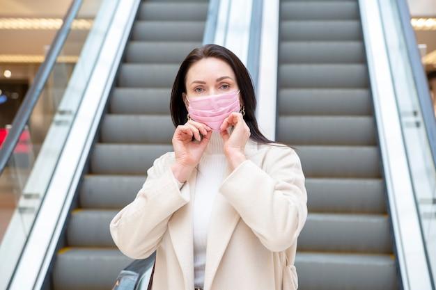 Schöne frau, die rosafarbene medizinische maske in ihrem gesicht mit den händen auf ihrem gesicht vor dem hintergrund der rolltreppe an einem öffentlichen ort berührt.