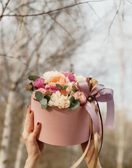 Schöne frau, die rosafarbenen kasten mit blumen anhält. geschenk zum frauentag.