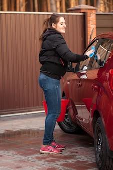 Schöne frau, die rotes auto am hof des hauses wäscht