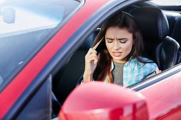 Schöne frau, die rotes auto fährt, sprechen während des fahrens. profil der verärgerten frau, die rotes auto fährt, stress während der fahrt. kopf und schultern der brünetten frau im auto