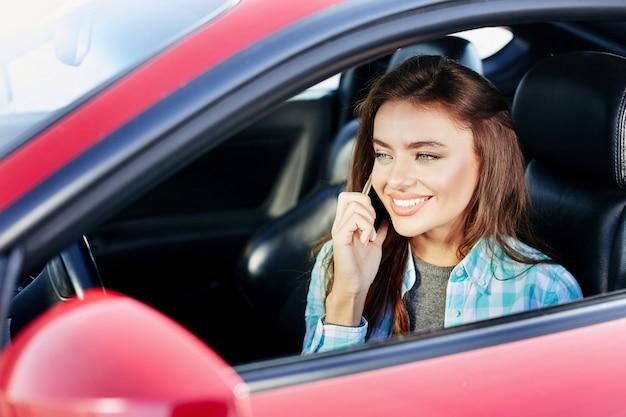 Schöne frau, die rotes auto fährt, sprechen während des fahrens. zur seite schauen und lächeln und telefonieren. kopf und schultern, neues auto kaufen