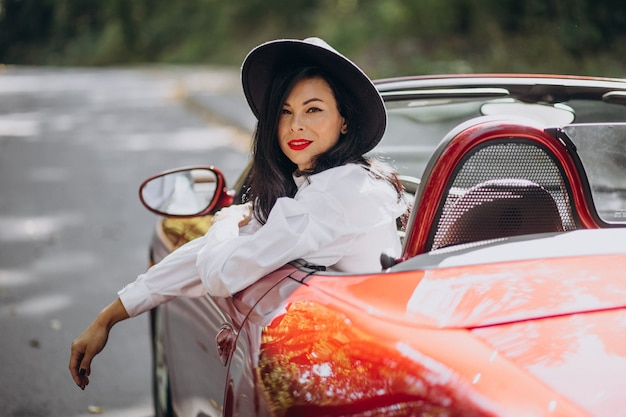 Schöne frau, die rotes cabrio fährt