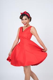 Schöne frau, die rotes kleid im studio trägt