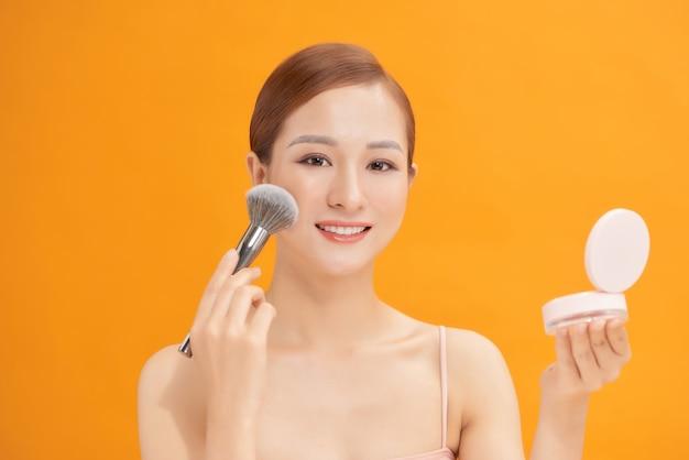 Schöne frau, die rouge auf ihre wange mit einem großen kosmetikpinsel anwendet, während ein kompakter spiegel vor ihr lokalisiert auf gelb hält