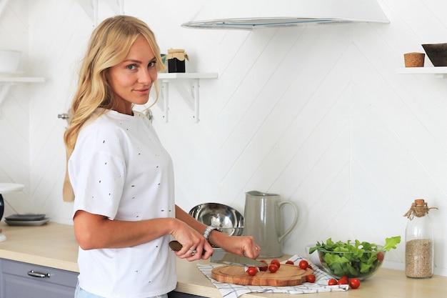 Schöne frau, die salat in der küche, tomaten mit einem großen messer schneiden kocht.