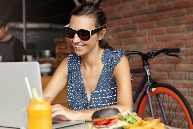 Schöne frau, die schatten trägt, die vor offenem laptop sitzen und videoanruf machen