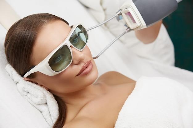 Schöne frau, die schutzbrille trägt, die im weißen spa-salon liegt und laserverjüngung erhält, erstaunliches mädchen, das gesichtspflege hat
