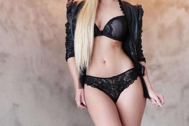 Schöne frau, die schwarze lederjacke und sexy schwarze dessous trägt