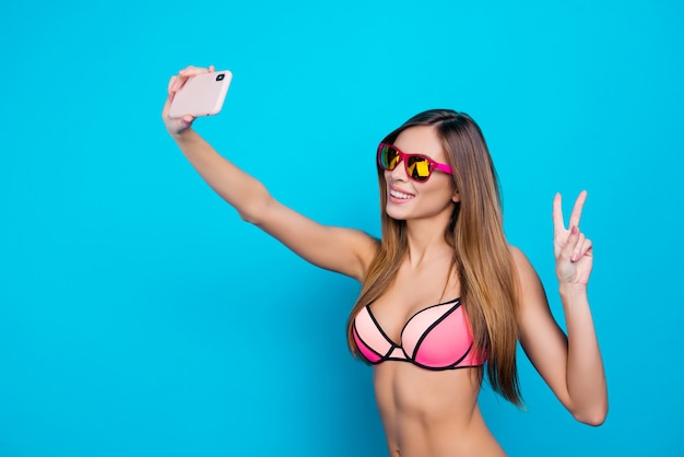 Schöne frau, die selfie im bikini mit smartphone nimmt