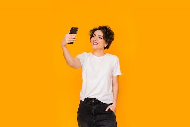 Schöne frau, die selfie zu hause nimmt. junges süßes mädchen, das über videolink auf einem mobiltelefon mit freunden oder verwandten spricht. glückliche frau mit smartphone für videoanruf freunde und eltern.