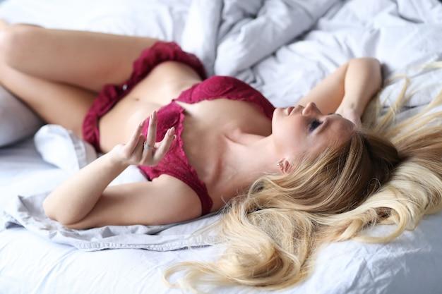 Schöne frau, die sexy rote dessous auf dem bett trägt