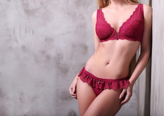Schöne frau, die sexy rote dessous trägt