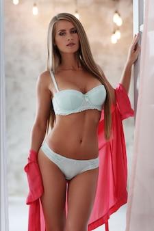 Schöne frau, die sexy unterwäsche und seidengewand trägt