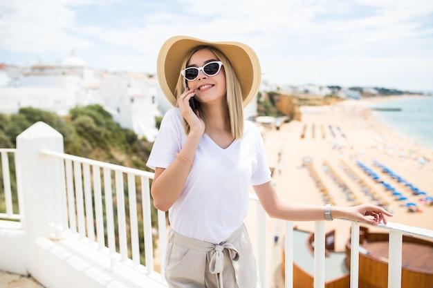 Schöne frau, die sich auf das terrassengeländer stützt, sich entspannt und einen anruf hat