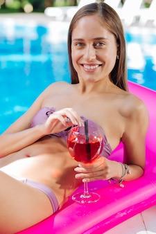 Schöne frau, die sich entspannt fühlt, während sie auf luftmatratze im pool liegt und cocktail trinkt