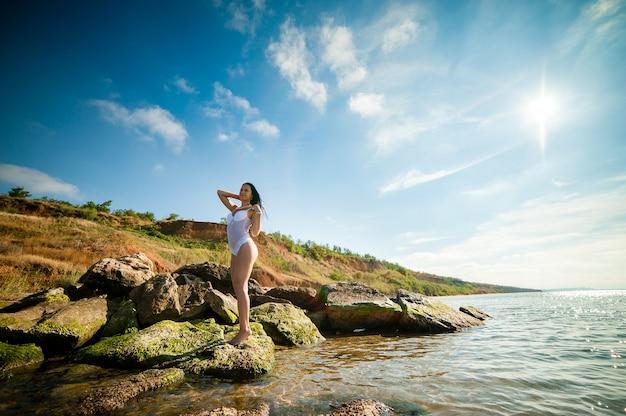 Schöne frau, die sich im meer sonnt und schwimmt