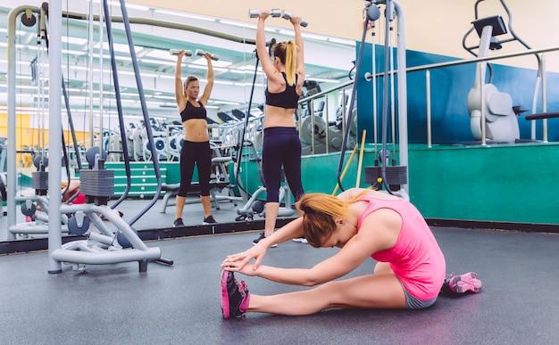 Schöne frau, die sich in einem fitnesscenter ausdehnt und eine freundin macht übungen mit hanteln im hintergrund