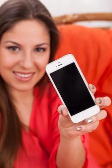 Schöne frau, die smartphone anhält