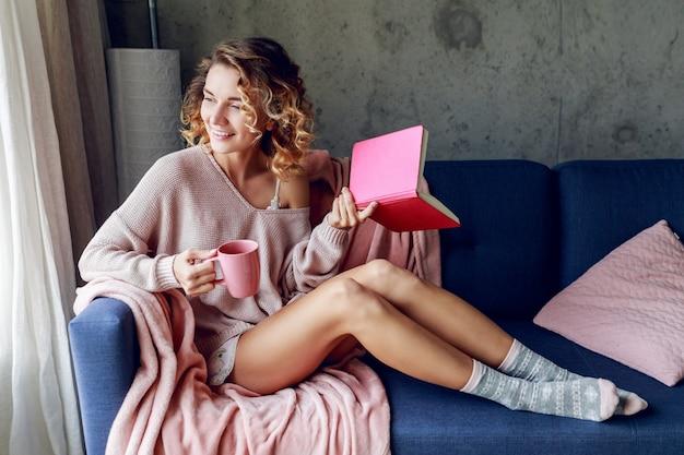 Schöne frau, die sonnigen morgen zu hause genießt, lieblingsbuch hält, kaffee trinkt. warme gemütliche stimmung. rosa weiche farben.