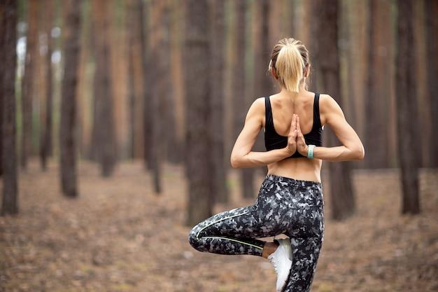 Schöne frau, die steht und yoga im wald tut. übungs- und meditationskonzept. bezahle oder erhöhe das handkonzept. kiefernholz im sommerthema. rückansicht.