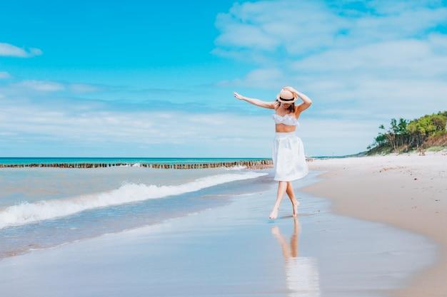 Schöne frau, die strohhut und weißen badeanzug und rock trägt, die entlang der brandungslinie am strand nahe wellen gehen.