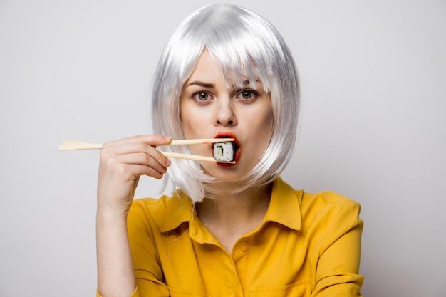 Schöne frau, die sushi isst