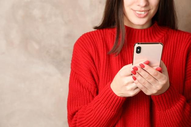 Schöne frau, die telefon auf braunem hintergrund benutzt. platz für text