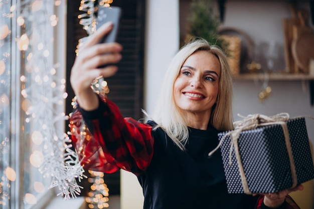 Schöne frau, die telefon durch fenster auf weihnachten verwendet