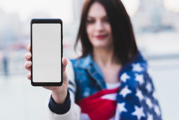Schöne frau, die telefon mit weißem bildschirm zeigt