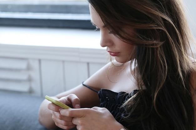 Schöne frau, die texing auf ihrem telefon aufwirft