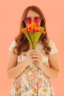 Schöne frau, die tulpenvoransicht hält