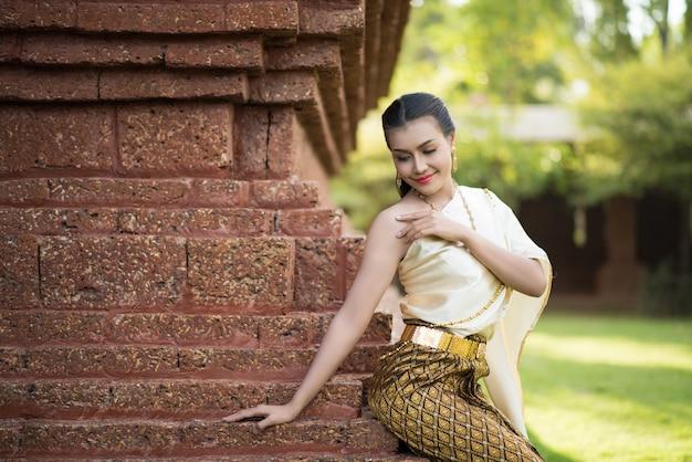Schöne frau, die typisches thailändisches kleid trägt